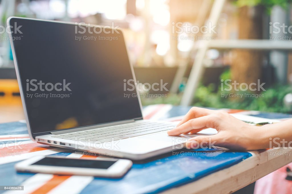 Women's hand using a notebook computer blank screen on a wooden desk. stock photo