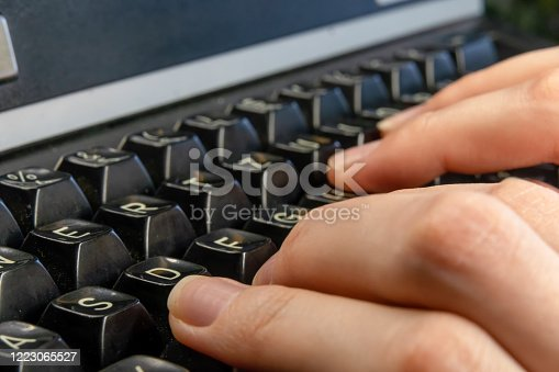 Women's hands are typing on an old dirty black typewriter close up