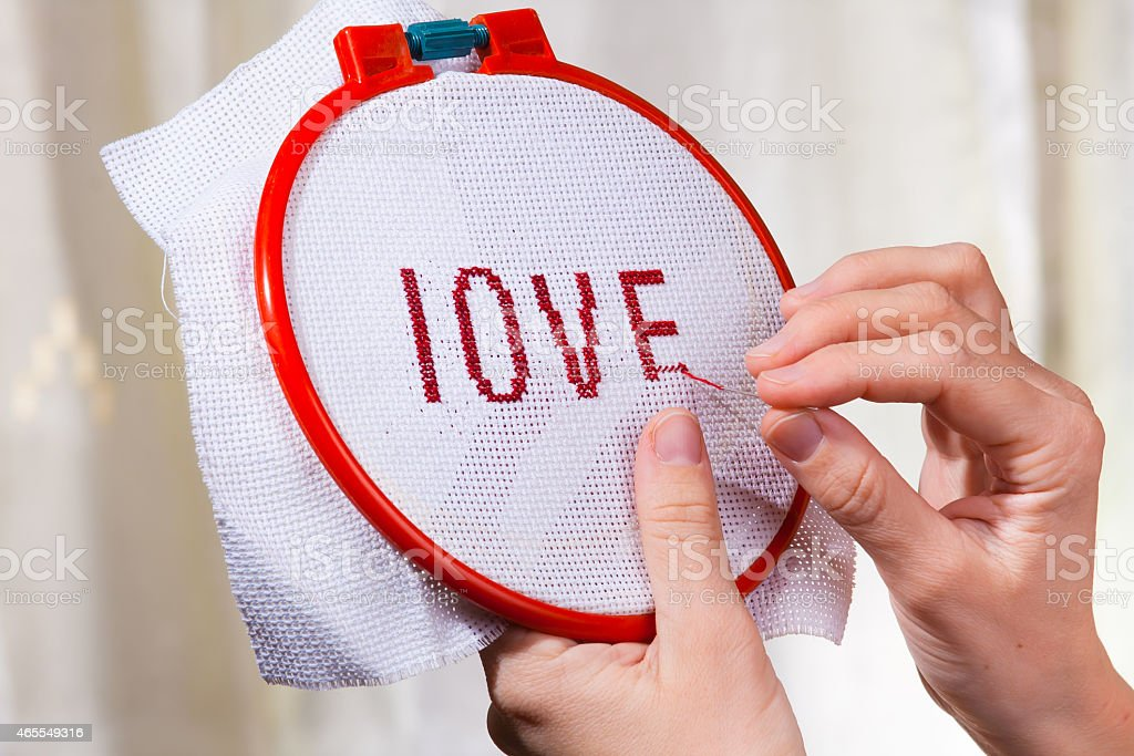 Women's hands embroider a word love stock photo