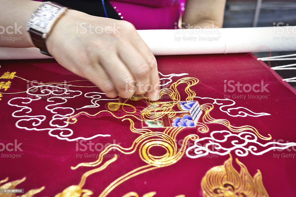Women's hands embroidered on the  patterns of dragon royalty-free stock photo