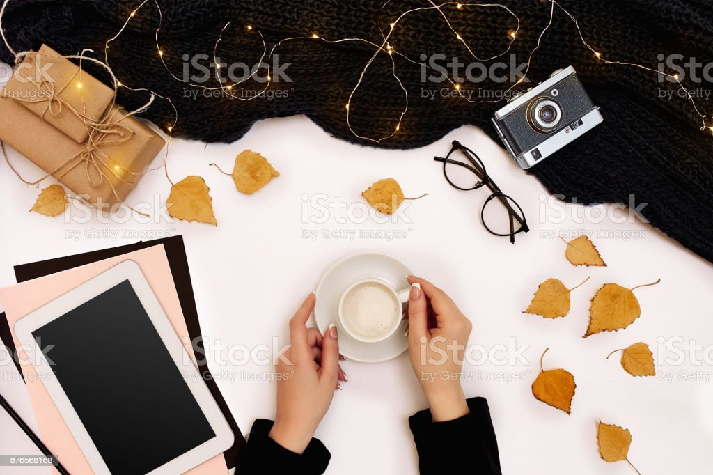 Women's hands hold a cup of coffee, scarf on white background. Autumn or Winter concept. Flat lay, top view stock photo