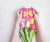 women's hands hold a gift box, a bouquet of tulips on a wooden background