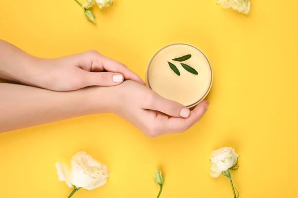 womens hands hold a jar of natural cosmetics. cream. eco cosmetics. hands near flowers on a yellow background. cream in the hands. skin care. place for an inscription. flat lay - cuticle stock pictures, royalty-free photos & images