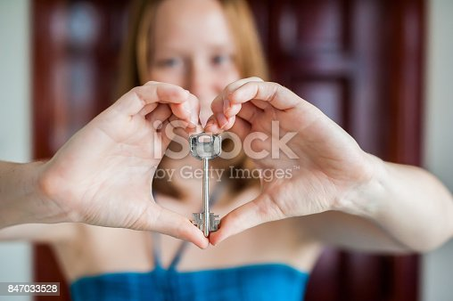 Women's hands hold house key in the form of heart on the background of a wooden door. Owning real estate concept.