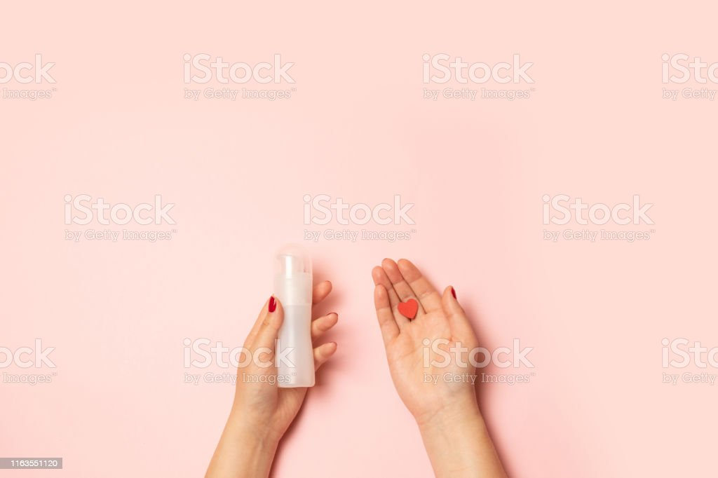 Womens hands hold intimate grease and a red heart shape on a pink background Selling love concept. Womens hands hold intimate grease and a red heart shape on a pink background Adult Stock Photo
