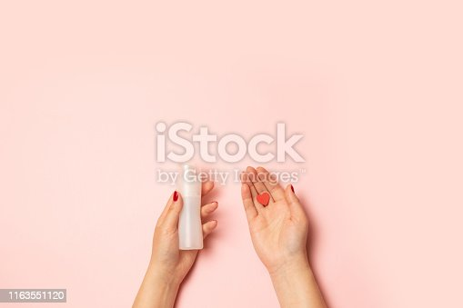 Selling love concept. Womens hands hold intimate grease and a red heart shape on a pink background