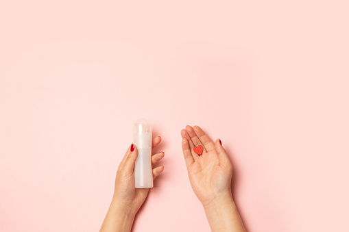 Womens Hands Hold Intimate Grease And A Red Heart Shape On A Pink Background Stock Photo - Download Image Now