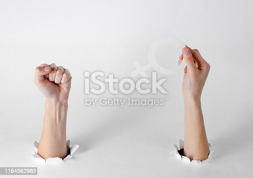istock Women's hands hold the feminist gender symbol and fist through the torn holes of a white background. Creative art 1164562983