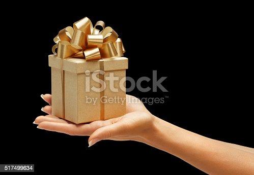 istock Women's hands holding gift box 517499634