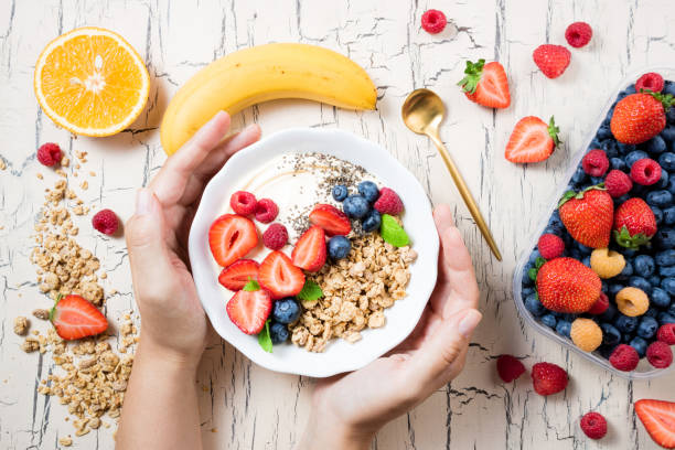 women's hands holding granola with berries, fruits, yoghurt and coffee for breakfast. cereal oats with strawberries, blueberries and raspberries for healthy eating. top view - porridge foto e immagini stock