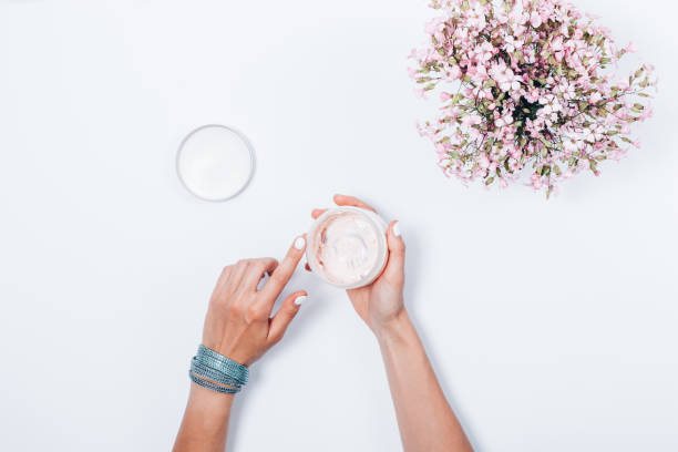 women's hands holding opened jar of cosmetic cream - cuticle stock pictures, royalty-free photos & images