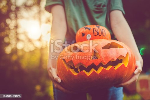Women's hands holding pumpkins at Halloween in autumn