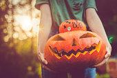 Women's hands holding pumpkins at Halloween in autumn