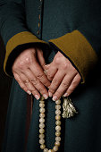 Women's hands in medieval dress (green woolen dress) holding a marble rosary