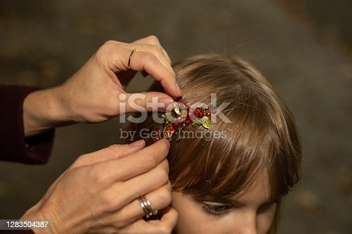 Women's hands of a mother or caregiver carefully fasten a hair clip on the hair of a little girl. Outdoors close-up photo. Hair accessories