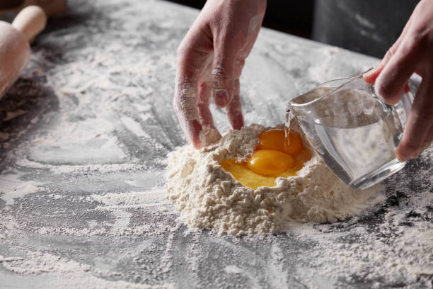 women's hands pours water into the flour on the kitchen table. Preparation of dough for baking stock photo