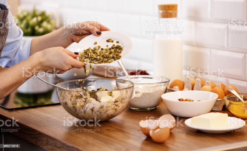 women's hands prepare dough with nuts and seeds for cookies royalty-free stock photo