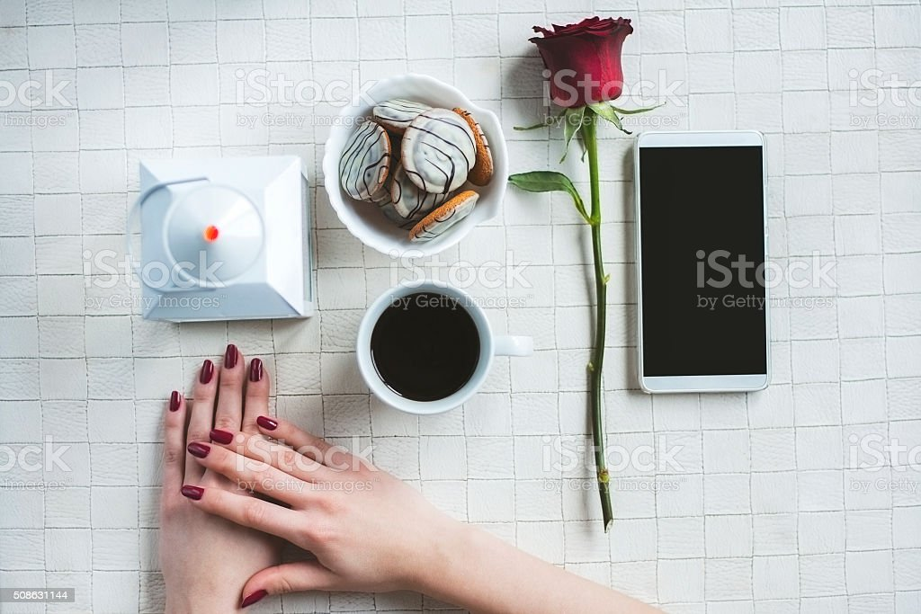 Women's hands, rose, mobile phone and coffee stock photo