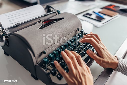 Women's hands typing on an old typewriter.