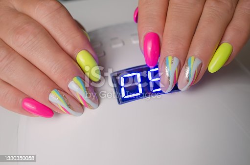 istock Women's hands with a beautiful summer manicure on the background of a lamp. 1330350058