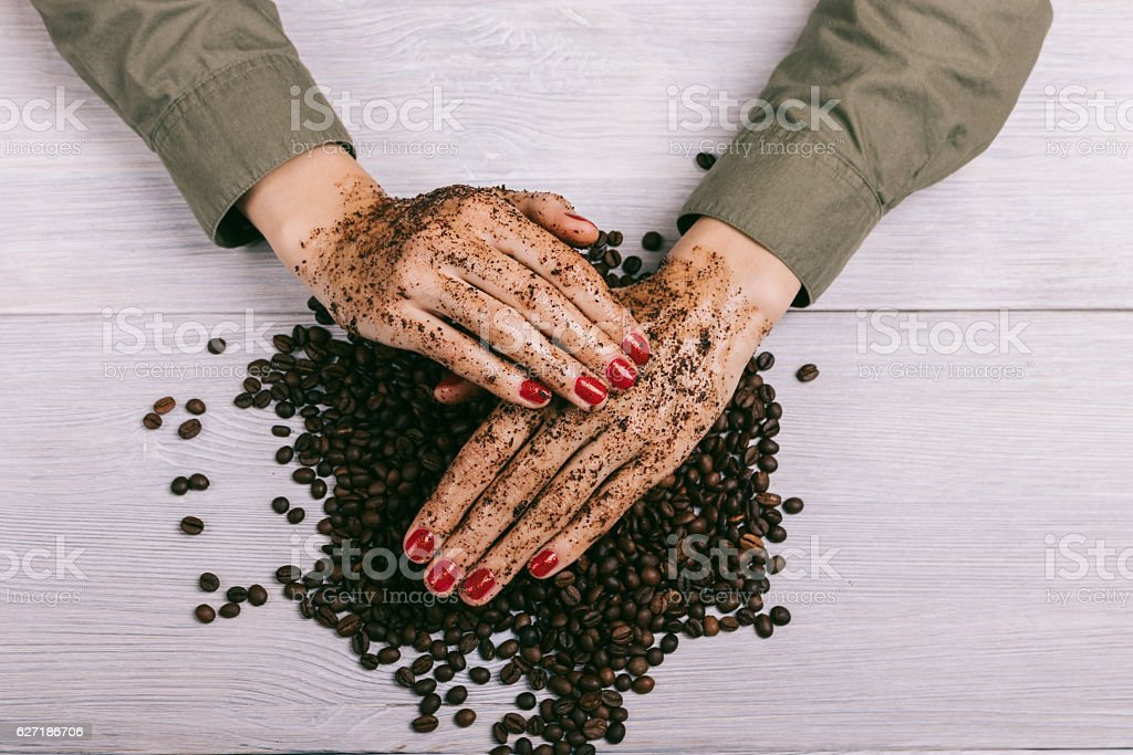 Women's hands with red nail polish applied the coffee scrub stock photo