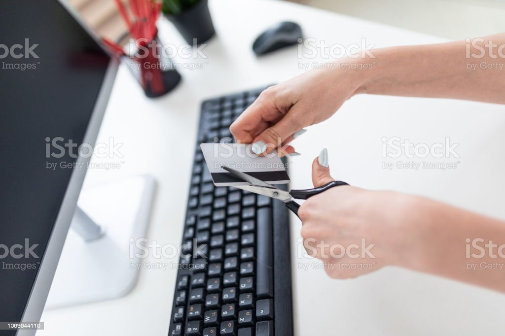Women's hands with scissors cut credit card. stock photo
