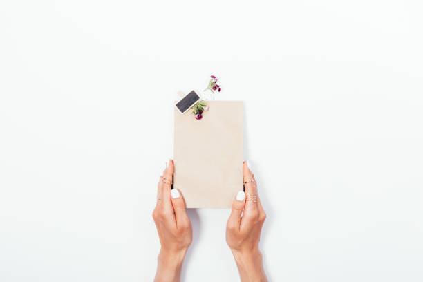 Mãos femininas com manicure branco mantém o saco de papel - foto de acervo