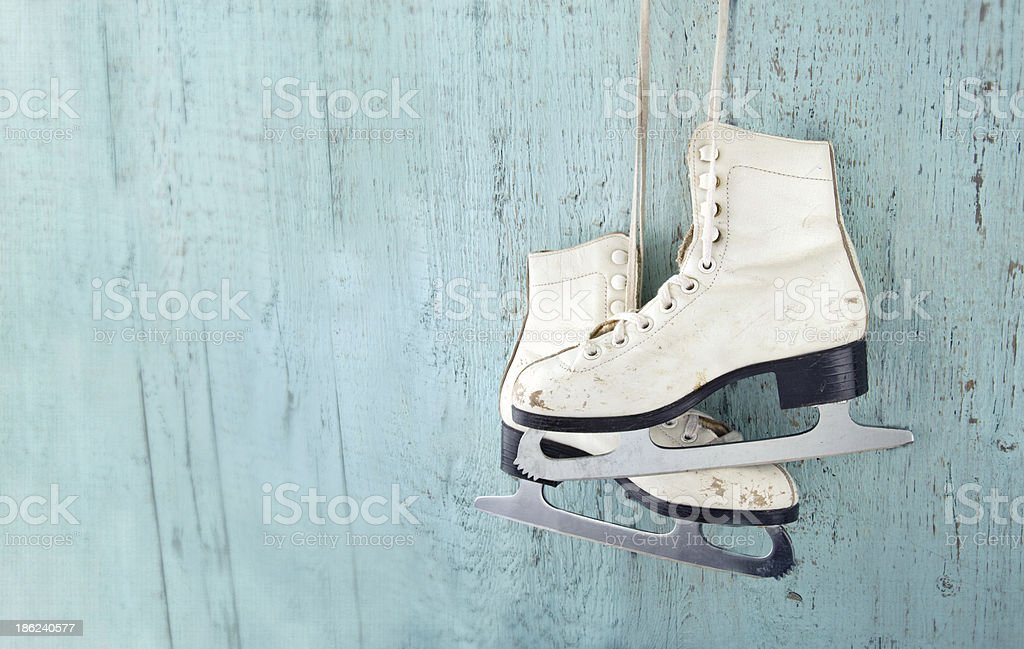 Women's ice skates hanging on blue wooden background stock photo