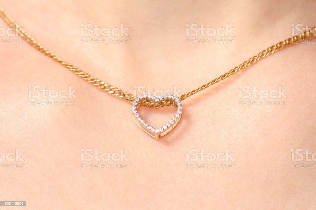 Women's jewelry on the neck gold chain pendant heart stock photo