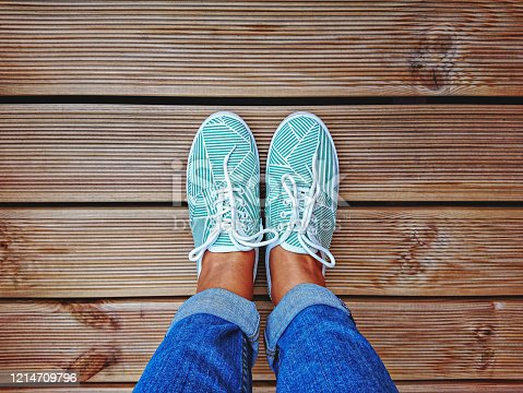 Women's legs in mint green sneakers on terrace board with copy space. Top view and personal point of view