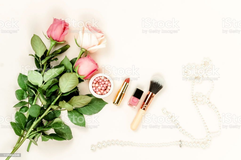 Women\'s makeup products, accessories and pink flowers roses top view...