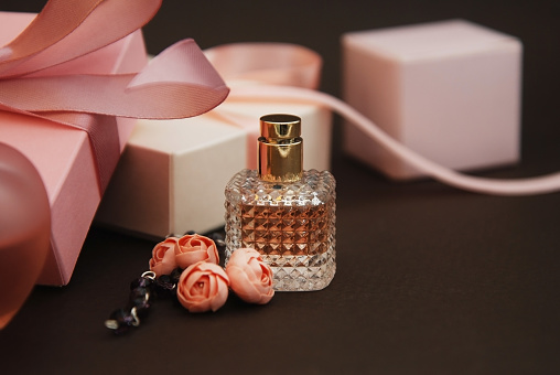 Women's Pink Perfume in Beautiful Bottle and Artificialt Flowers Bracelet on Brown Background with gift boxes.