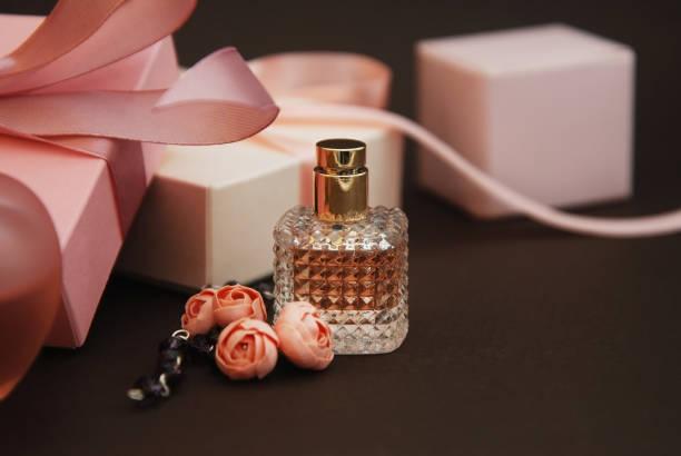 damskie różowe perfumy w pięknej butelce i sztucznej bransoletce z kwiatami na brązowym tle z pudełkami na tle. - perfumowany zdjęcia i obrazy z banku zdjęć
