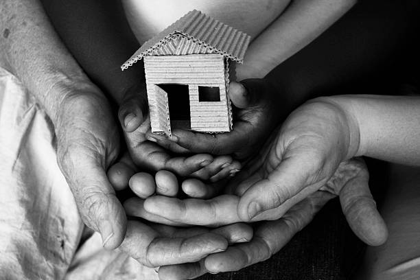 women's shelter three layers of hands supporting a home (shot in b/w) sheltering stock pictures, royalty-free photos & images
