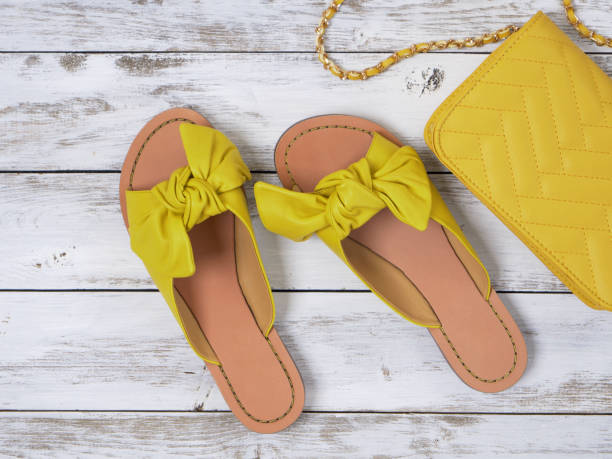Womens shoes (yellow leather sandals with knotted bow). Fashion outfit, spring summer collection. Shopping concept. Flat lay, view from above stock photo
