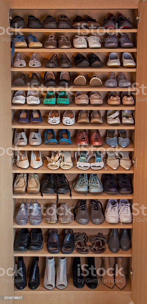 Women's shoes, variety of footwear on shelves. stock photo