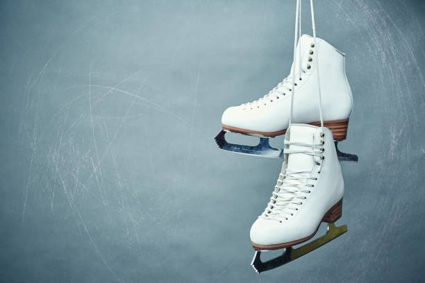 Women's skates with laces on a gray background. A pair of female white skates on a gray background. ice skating stock pictures, royalty-free photos & images