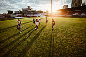 Large group of teenage soccer players playing a match on a stadium at sunset.