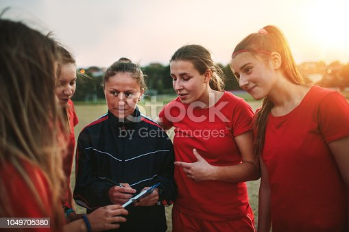 Women's soccer team talking with their female coach on training.