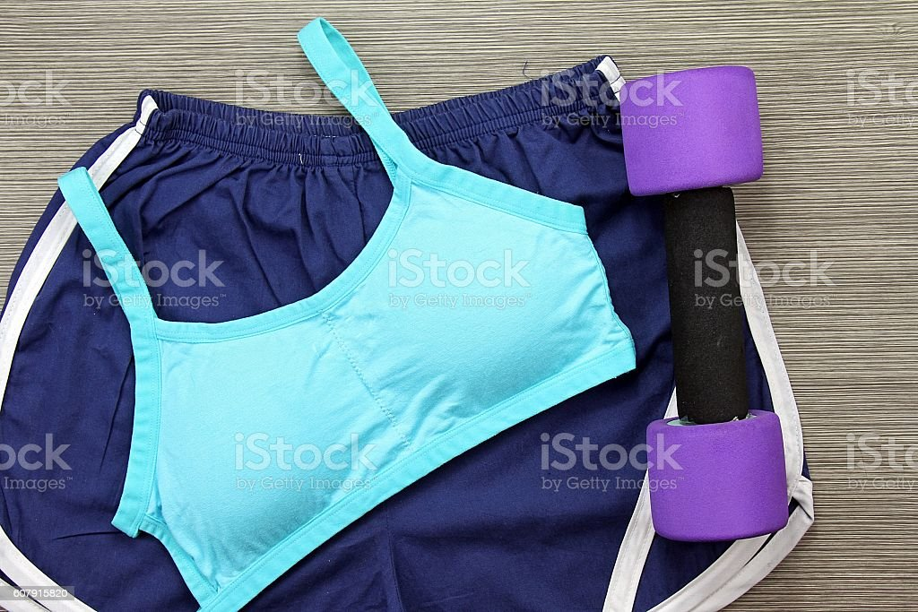Women's sports bra and Dumbbell. Fitness wear and equipment. stock photo