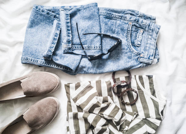 women's spring, summer fashion clothes set in pastel colors - mom's jeans, cotton striped pullover, suede sneakers, leather bracelets and sunglasses on a light background, top view. flat lay, fashion concept - spring fashion stock pictures, royalty-free photos & images