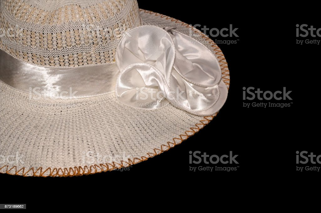 Women's straw hat with the white ribbon isolated on black backgr stock photo