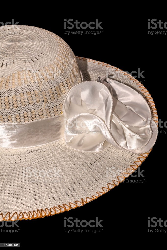 Women's straw hat with the white ribbon isolated on black background. The file includes a clipping path so it is easy to work. stock photo