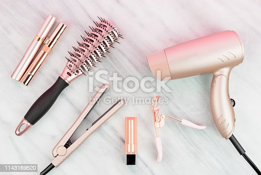istock Women's styling tools and cosmetics in rose gold 1143169520