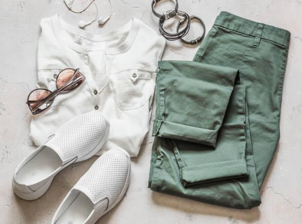 Sommerkleidung der Damen-Olivenwolltaschenhose, weißes, weißes, hultiges T-Shirt, weiße Lederschuhe, Sonnenbrille, Armbänder auf hellem Hintergrund, Top-Aussicht – Foto