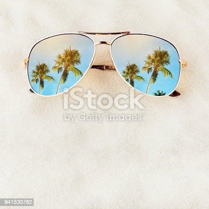 Women's Sunglasses no title on the sand with space for text, top view. Journey to the sea