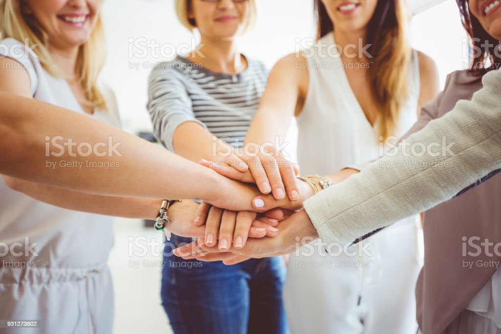 Women's team. Group of happy women joining hands Women's team. Group of happy woman joining hands and laughing. Close up of hands. Adult Stock Photo