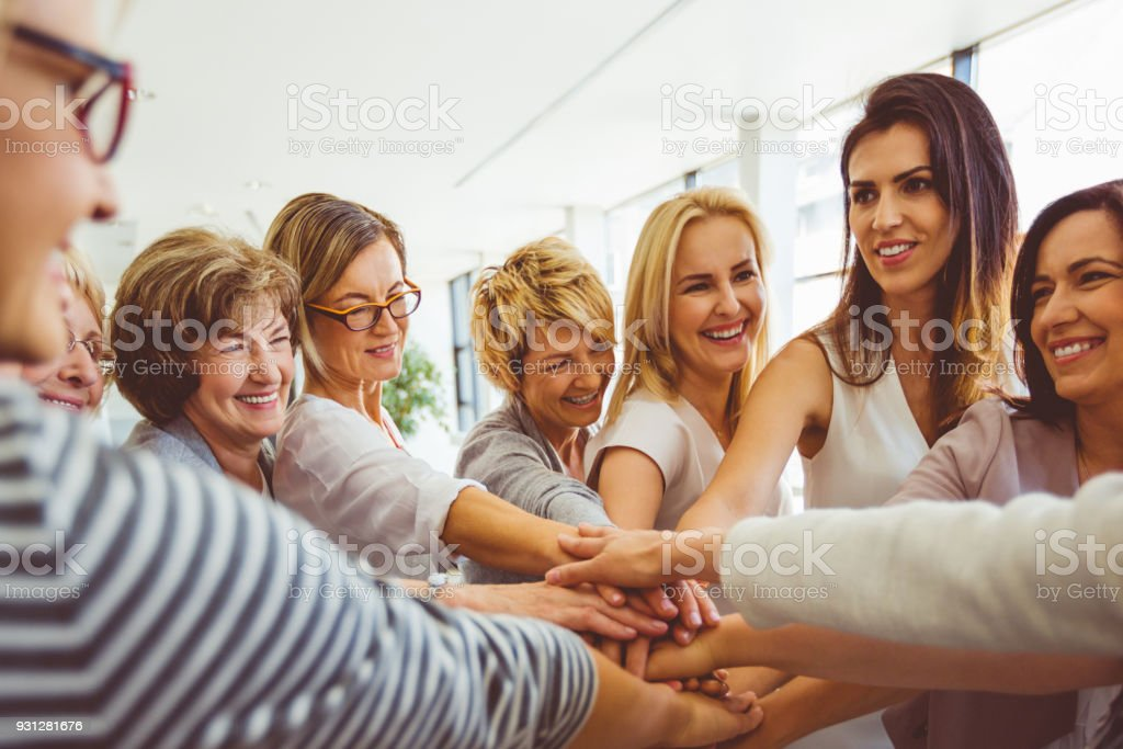 Women's team. Group of happy women joining hands Women's team. Group of happy woman joining hands and laughing. Adult Stock Photo
