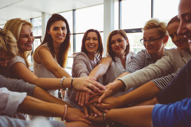 Women's team. Group of happy women joining hands Women's team. Group of happy woman joining hands and laughing. women's rights stock pictures, royalty-free photos & images