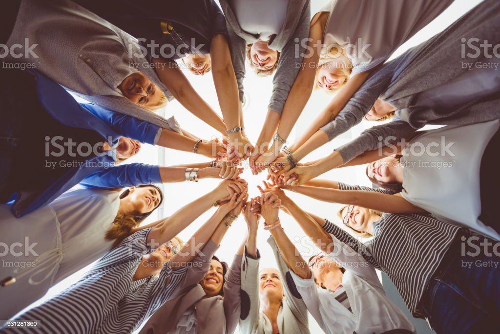 Women's team. Group of women holding hands Women's team. Large group of woman holding hands. Low angle view. Adult Stock Photo